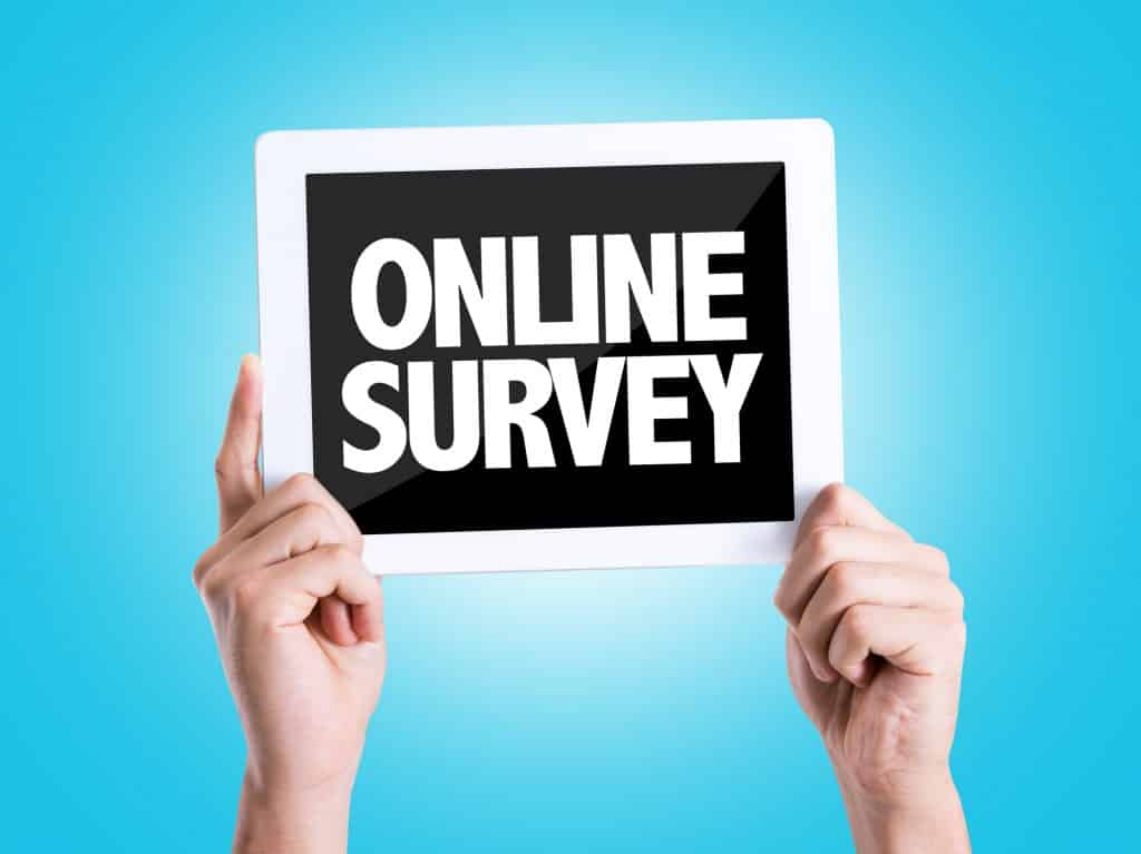 person holding an online survey sign