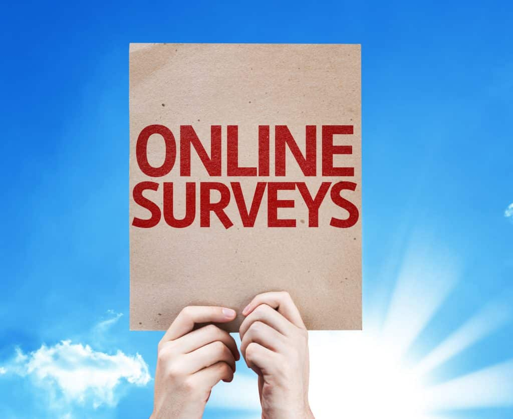 person holding an online surveys sign in hands