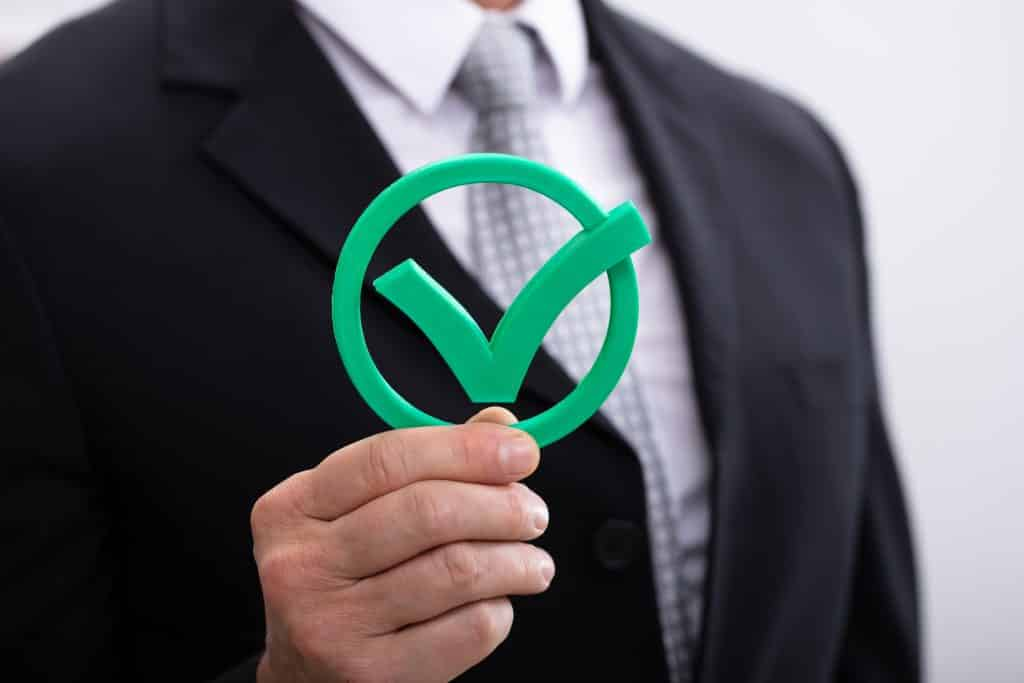 man holding an online survey panel checkmark