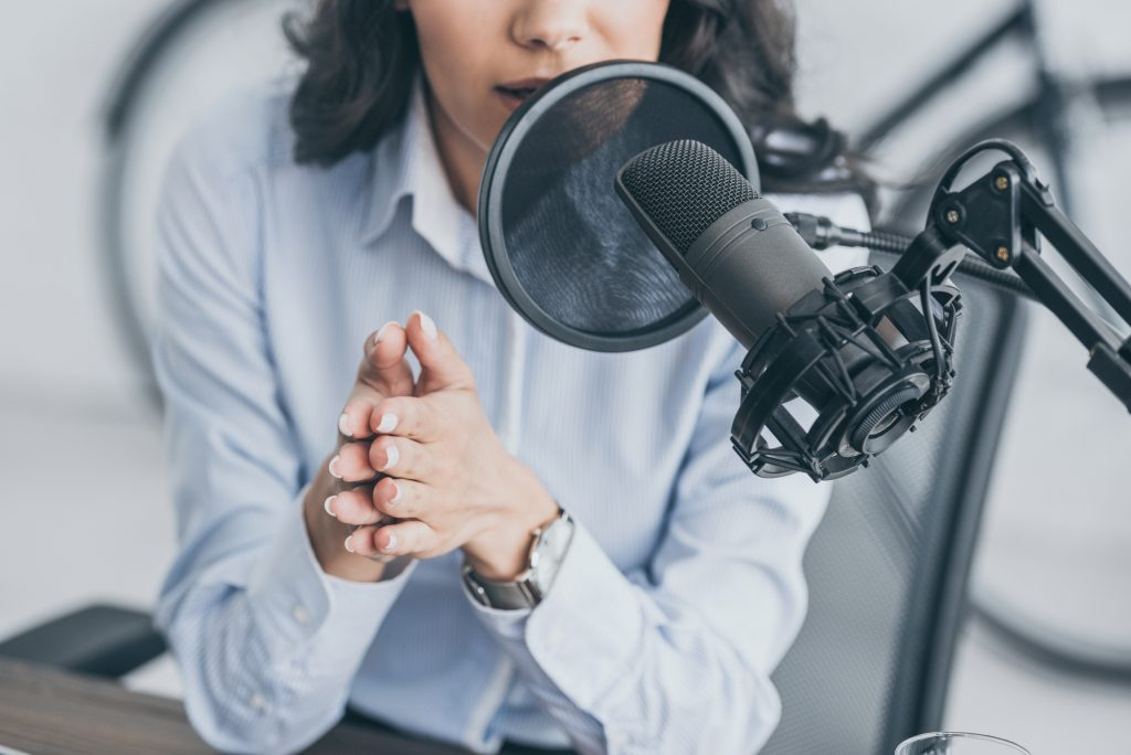 woman recording a podcast on a microphone